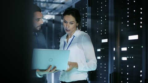 Male IT Specialist Shows Information on a Laptop to Female Server Technician. They're Standing in Data Center. Shot on RED EPIC-W 8K Helium Cinema Camera.