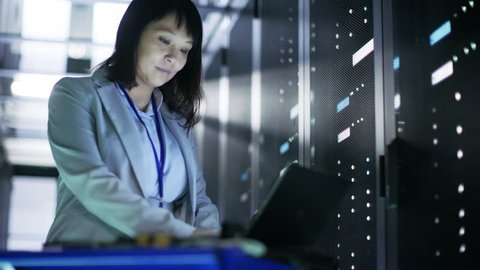 Asian Female IT Engineer Working on a Crash Cart Laptop, She Scans Hard Drives. She's in Big Data Center Full of Rack Servers. Shot on RED EPIC-W 8K Helium Cinema Camera.