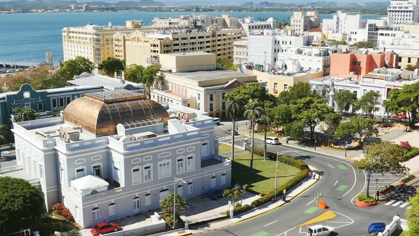 SAN JUAN, PUERTO RICO - MARCH 5, 2017: Establishing shot-Traffic on Ave Munoz Rivera passes the Antiguo Casino and Jose Julian Acosta School in San Juan Puerto Rico