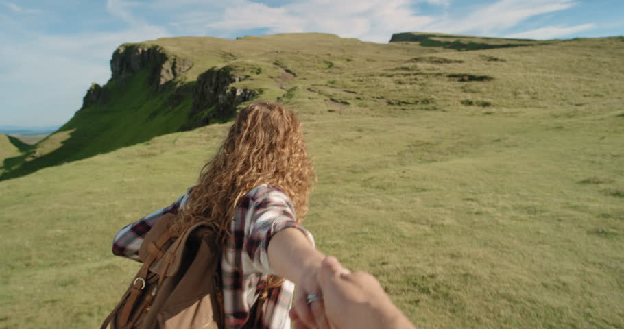 Young couple holding hands woman leading boyfriends walking towards mountain POV travel concept | Shutterstock Video #25252889