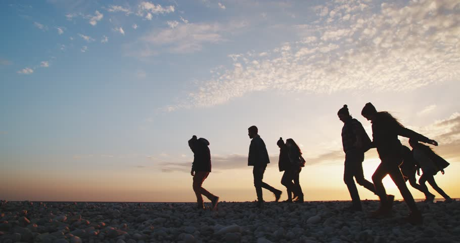 Group of hipster people walking together on a beach with pebbles in winter at sunset