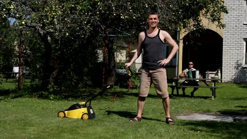 Young caucasian man mowing lawn by lawnmower. Freddie Mercury ''I want to break free'' parody. Funny, humor, humorous.