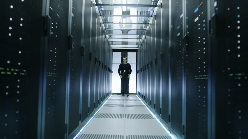 Frontal View of IT Engineer Walking Through Data Center with Working Rack Servers. Shot on RED EPIC-W 8K Helium Cinema Camera.   Shutterstock HD Video #25323410