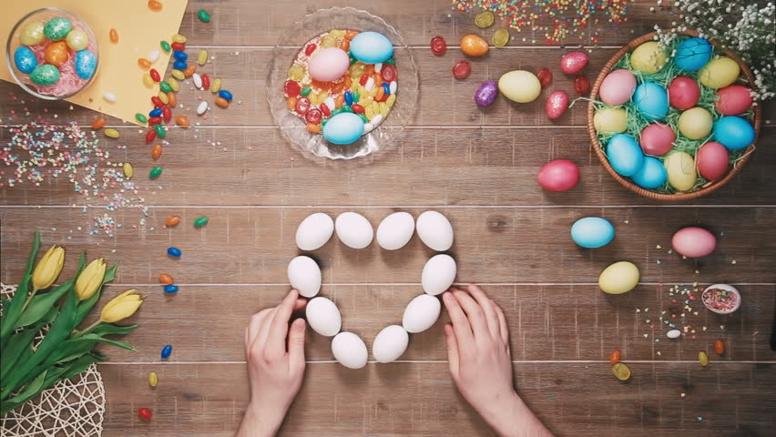 Man making heart shape with easter eggs on table decorated with easter eggs. Top view | Shutterstock HD Video #25342931