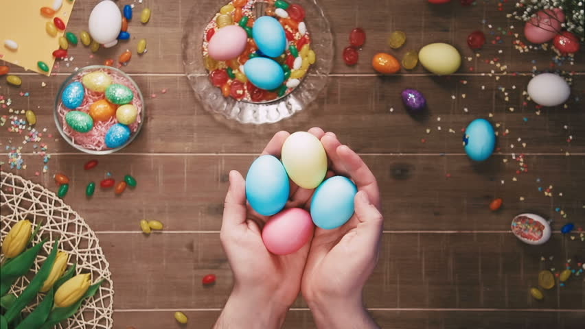 Hands holding easter eggs in front of the table decorated with easter eggs. Top view   Shutterstock HD Video #25342991