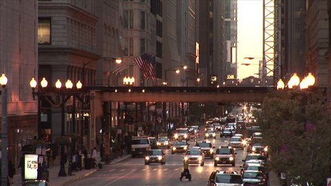 Chicago, IL - CIRCA September 2007: A busy street scene with an elevated train passing through the frame with traffic coming towards the camera at dusk