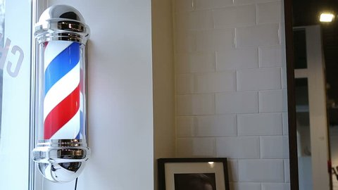Motion of barbershop pole spinning at barber shop. Barbershop pole on the wall.
