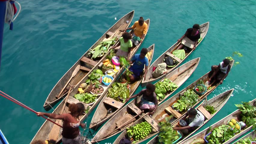 SOLOMON ISLANDS - CIRCA 2010: Many vendors in canoes sell fresh vegetables and fruits in the Solomon Islands circa 2010.