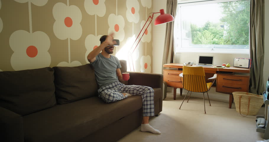 Young man wearing virtual reality headset sitting on sofa at home watching 360 video imagination concept | Shutterstock HD Video #25399001