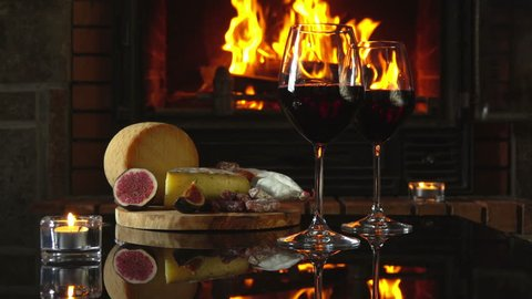 Hand puts on the table a glass of red wine. Reflection of the fire in the fireplace glass table with wine and snacks