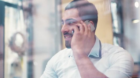 Young hot brunette guy sitting in the café by the window and drinking coffee, the phone is ringing, he picks up the phone and carelessly talks. Modern communication, technologies.