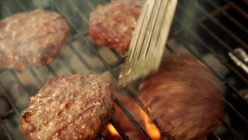 Flipping hamburgers on the grill