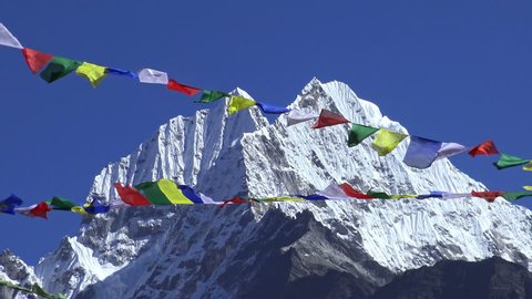 Tibetan prayer flags against white snowy mountain peak in the Everest region of Himalayan mountains, Nepal