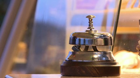 The call button at the reception.Male hand ringing silver service bell
