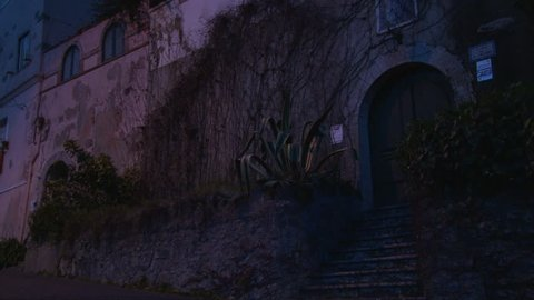 Ancient building walls, cars driving by road, evening dusk in small touristic town Sintra, Portugal, girl with a backpack walking come and observe old building