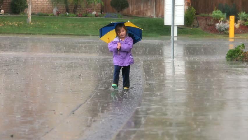 Young girl having fun walking in the rain