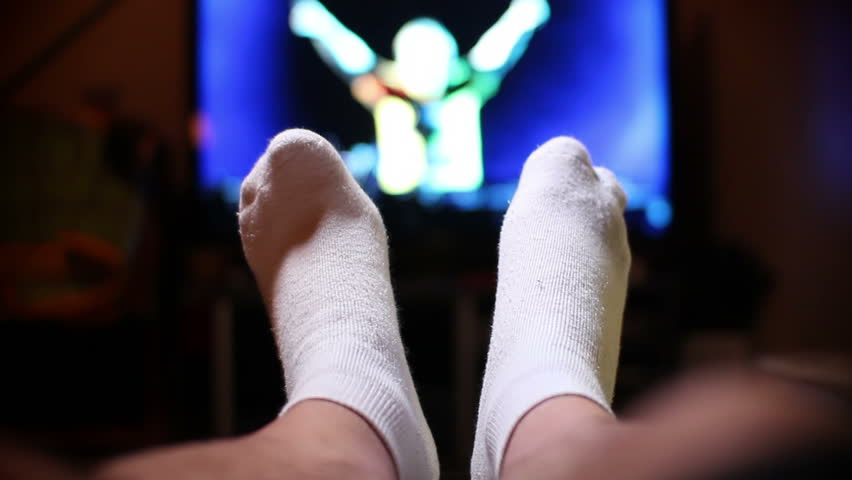 A man watches television, relaxing with his feet up.  Extreme shallow DOF. | Shutterstock HD Video #2546561