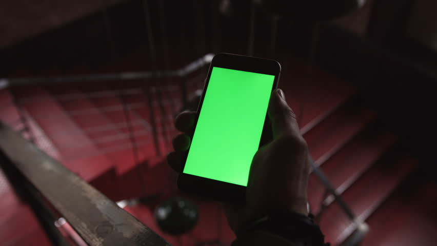 Close-up of a man holding and touching the phone with green screen in the background red stairs | Shutterstock HD Video #25491215