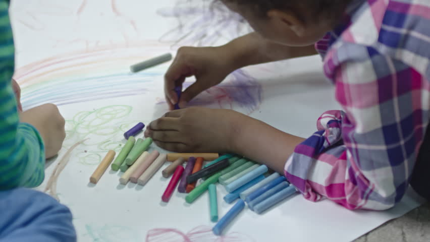 Slow motion shot of little kids sitting on the floor and drawing together on paper with colorful pieces of chalk. | Shutterstock HD Video #25511312