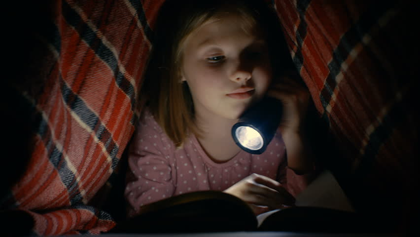 Smart Little Girl Reads Interesting Book with a Flashlight Under Blanket. Shot on RED EPIC-W 8K Helium Cinema Camera.