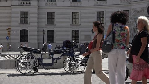 VIENNA - AUSTRIA, JULY 16, 2014, 4K Crowded old town icon, traditional horse chariot parking on busy street