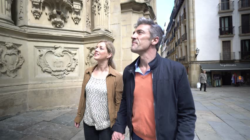 Couple of tourists visiting european city, passing by catholic chuch