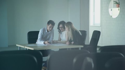 In an empty conference room, three employees work overtime for papers. In a large office of a large company, a man and a woman brainstorm to complete a management task. In the foreground there is a