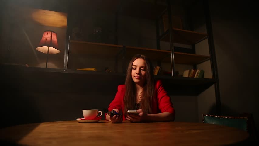 The girl in the red jacket Smoking the electronic cigarette and talking on a cell phone. | Shutterstock HD Video #25627331