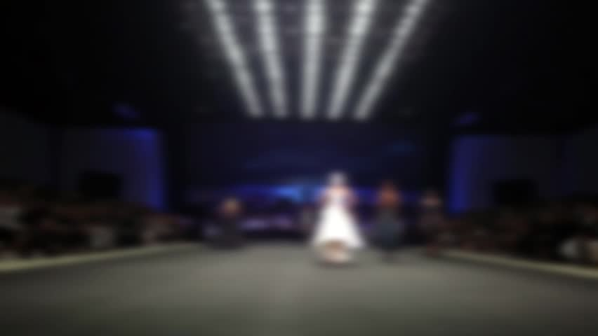 Blur Out of Focus of Fashion Show Runway Catwalk of Supermodels in Big Event Hall wide and stage lighting, full length model walk in dark atmosphere, lighting spot on path only