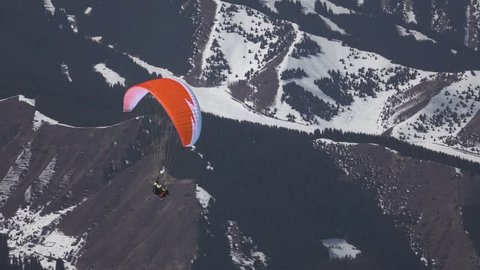 Flight of a tourist on a paraglider against the backdrop of beautiful mountains