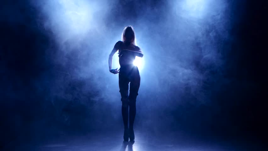 Slender blonde in leather lingerie dances. Silhouette on smoky background