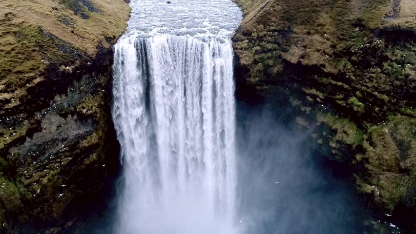 Aerial flight with drone over the famous  Skogar waterfall in Iceland. It is located on the South of the island. Image taken with action drone camera causing distortion and blur. Slow motion shot | Shutterstock HD Video #25673321
