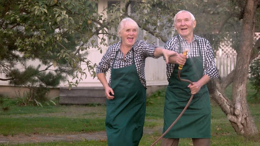 Elderly couple with garden hose. Old people having fun. | Shutterstock HD Video #25695023
