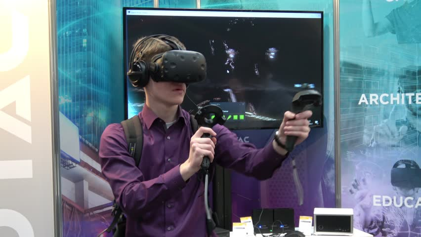 Hannover, Germany - March, 2017: Man playing video game in virtual reality headset and handheld controllers developed by HTC Vive on exhibition Cebit 2017 in Hannover Messe, Germany #25714091