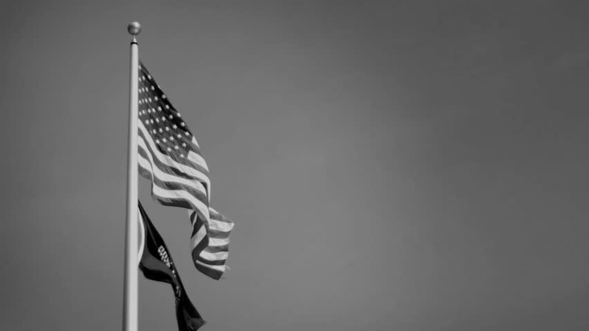 An American flag flowing with a Vietnam POW MIA Flag - Black and White Version