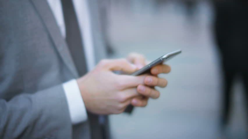 Businessman using smartphone in a crowded street. Technology. | Shutterstock HD Video #25718288