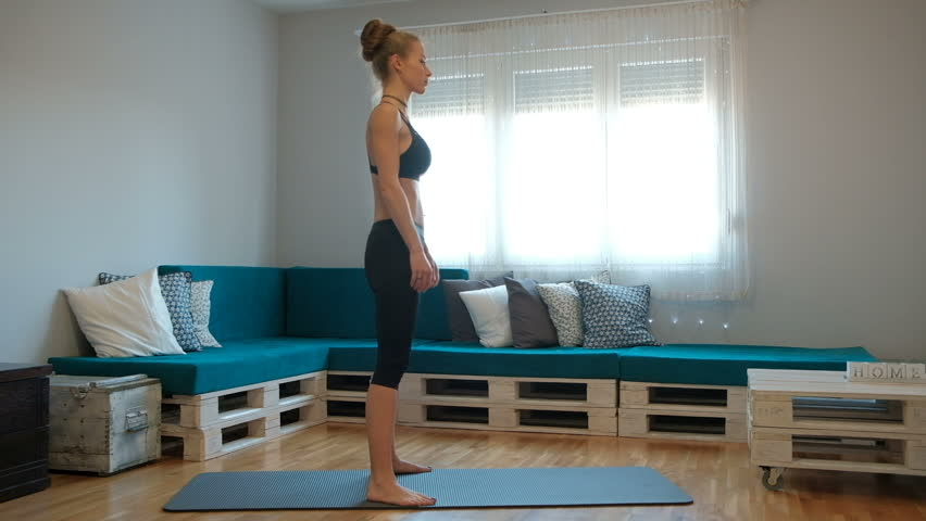 Young thin woman in training suit do exercise on mat indoor. In middle of room on special carpet female with long blond hair in black top and leggings stand, squat with straight hands in front of her