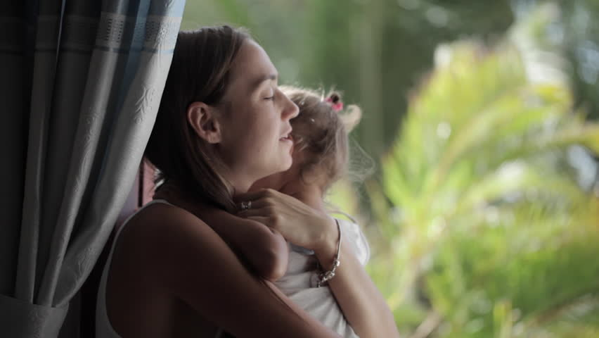 Pretty mother soothing and hugging crying baby girl when they sitting on windowsill with palm trees on the background