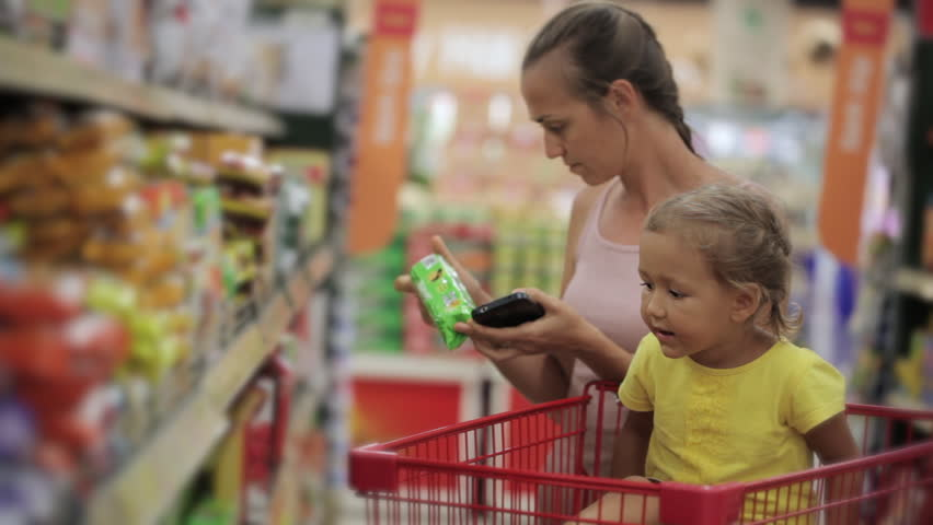 Young mother with little daughter selecting snacks in the sweets section at the supermarket | Shutterstock HD Video #25735601