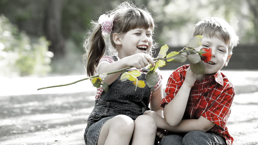 Two child speaking and boy present flower