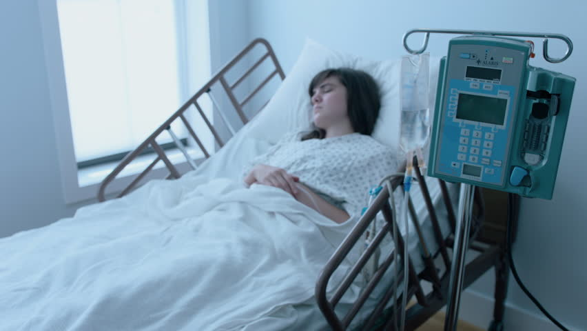A sick young woman with an IV recovering in a hospital bed next to a window, slow motion, 4K #25746611