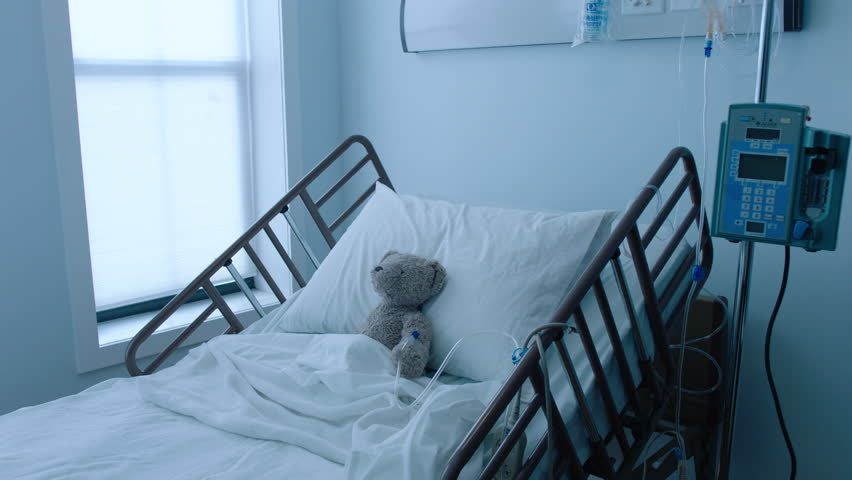 A teddybear stuffed animal with an IV recovering in a hospital bed next to a window, slow motion, 4K | Shutterstock HD Video #25746668