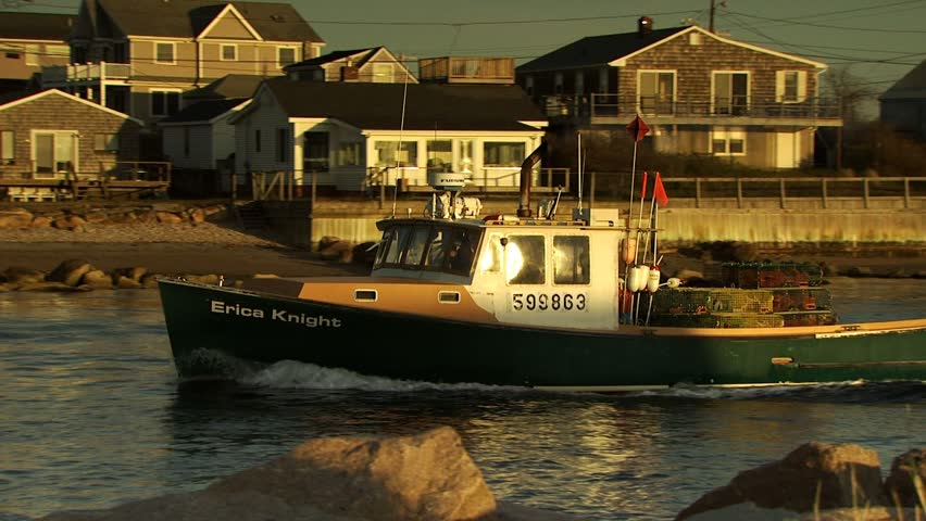 GALILEE, RHODE ISLAND - JUNE 13, 2008: Fishing boat leaving port at sunrise or sunset with lobster traps on deck