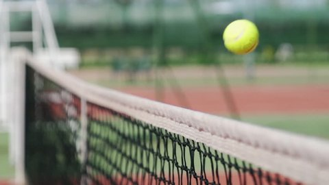 close up of tennis ball bouncing on the net scoring point slow motion
