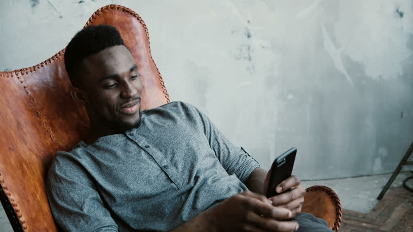 Portrait of African man sitting in chair, using Smartphone. Man reads messages and laughs. Guy typing massages, smiling | Shutterstock HD Video #25776491