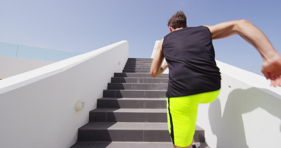 Running on stairs man doing run up on staircase. Male runner athlete climbing stairs in sport workout run outside.