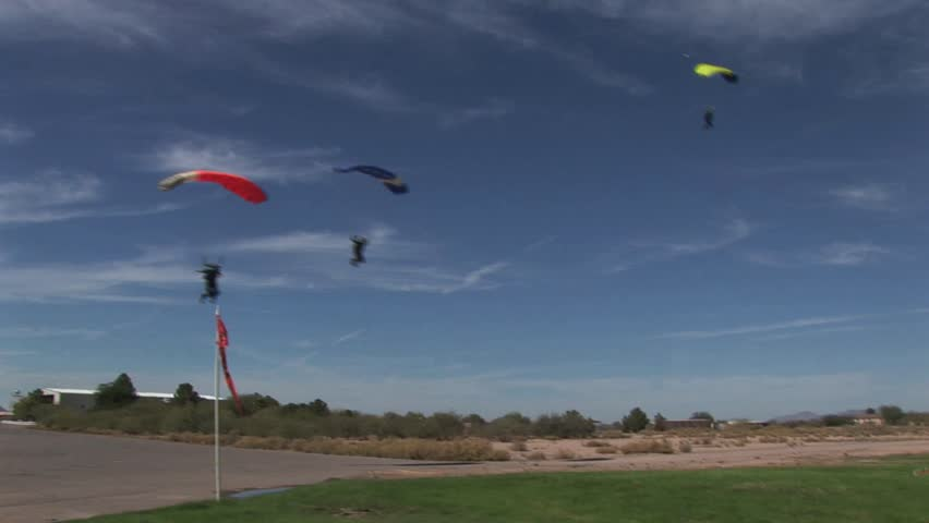 Three Skydivers Landing In A Field