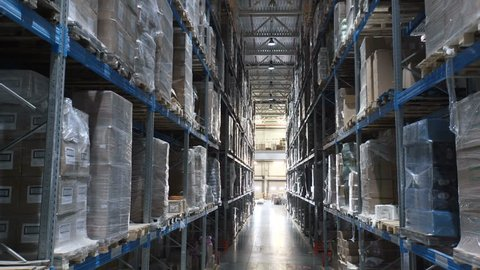 Camera shot of different materials in stockroom: racks indoor around: boxes, pallets, inventory, products, containers, merchandises. Logistics large place with transnational stuff to shipment process