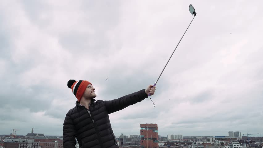Happy man,in colorful hat, taking selfie photo with cellphone on roof , 4K. | Shutterstock HD Video #25821341