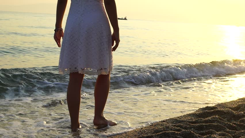 SLOW MOTION: Young woman in white dress walking alone on the beach in the sunset or sunrise. | Shutterstock HD Video #25842401